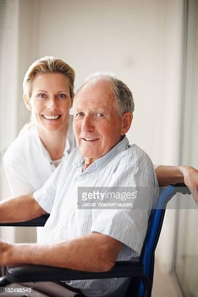 Anciano en la silla de ruedas con un personal de enfermería