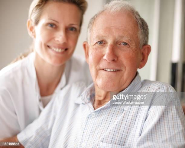 Elderly man on the wheelchair with a nurse