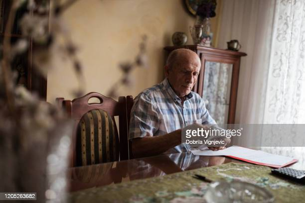 elderly man packing his pension money into an envelope - one senior man only stock pictures, royalty-free photos & images