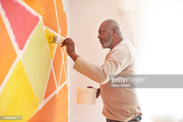 elderly man painting design on wall at home - expertise stock pictures, royalty-free photos & images