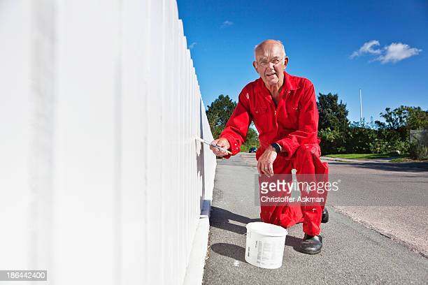 Elderly man painting fence
