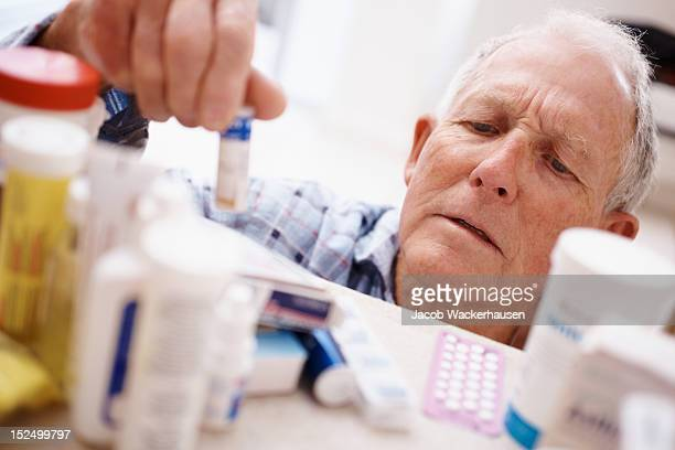 Elderly man picking medicine bottle from a shelf
