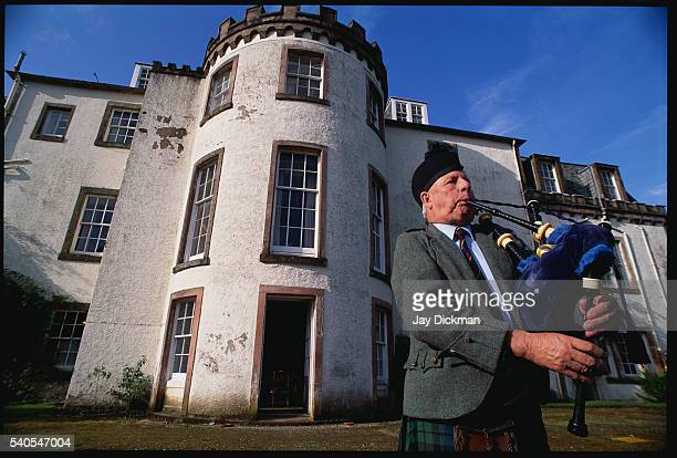 Elderly Man Playing Bagpipes Outside Mansion