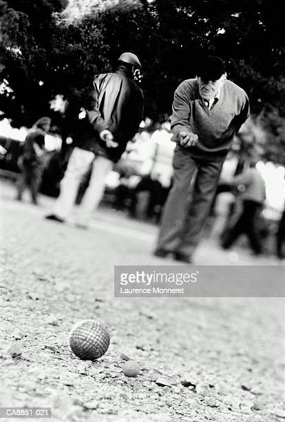 Elderly man playing boules, France (B&W)