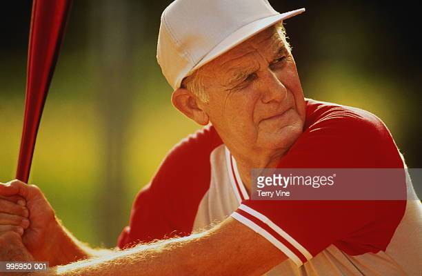 elderly man playing in senior softball game ready to bat - softball sport stock pictures, royalty-free photos & images