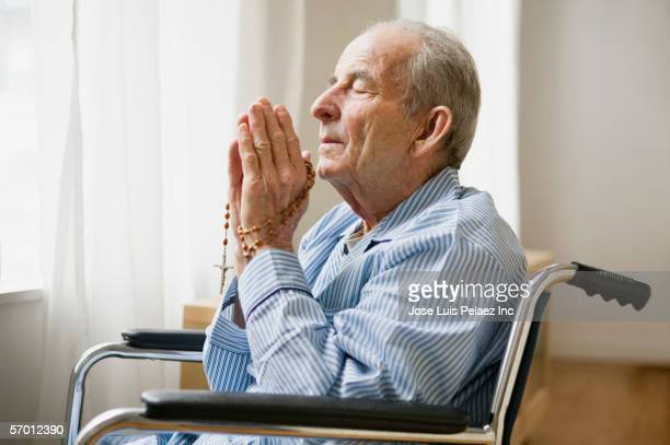 Elderly man praying with rosary beads