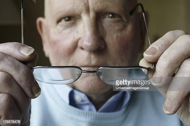 Elderly man putting on his glasses