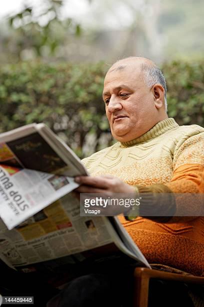 Elderly man reading a news paper