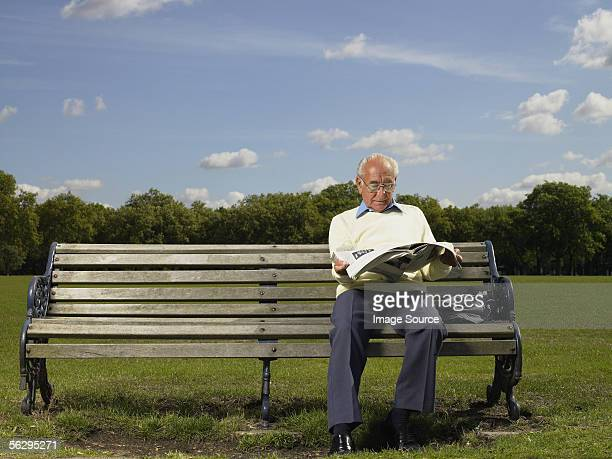 Elderly man reading a newspaper in a park