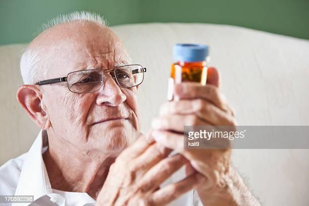 elderly man reading medicine bottle - tegenspoed stockfoto's en -beelden