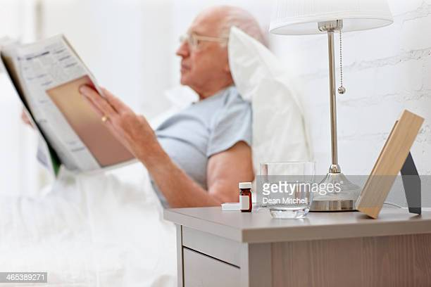 Elderly man reading newspaper in bedroom