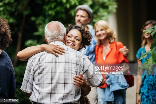 elderly man saying goodby to family after bbq - black family dinner stock photos and pictures