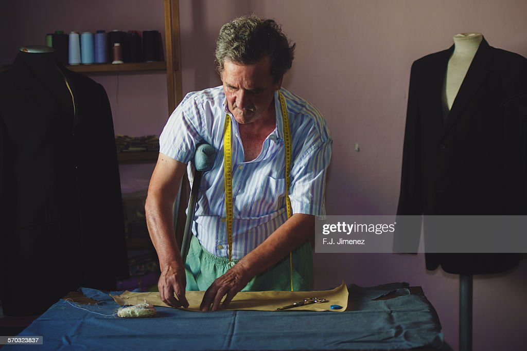 Elderly man sewing : Stock Photo
