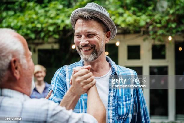 elderly man shaking hands with family member - pareja hombre mayor y mujer joven fotografías e imágenes de stock