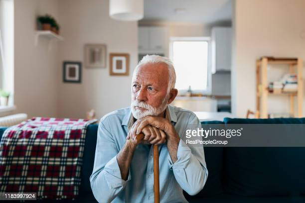 elderly man sitting alone at home - solitude stock pictures, royalty-free photos & images