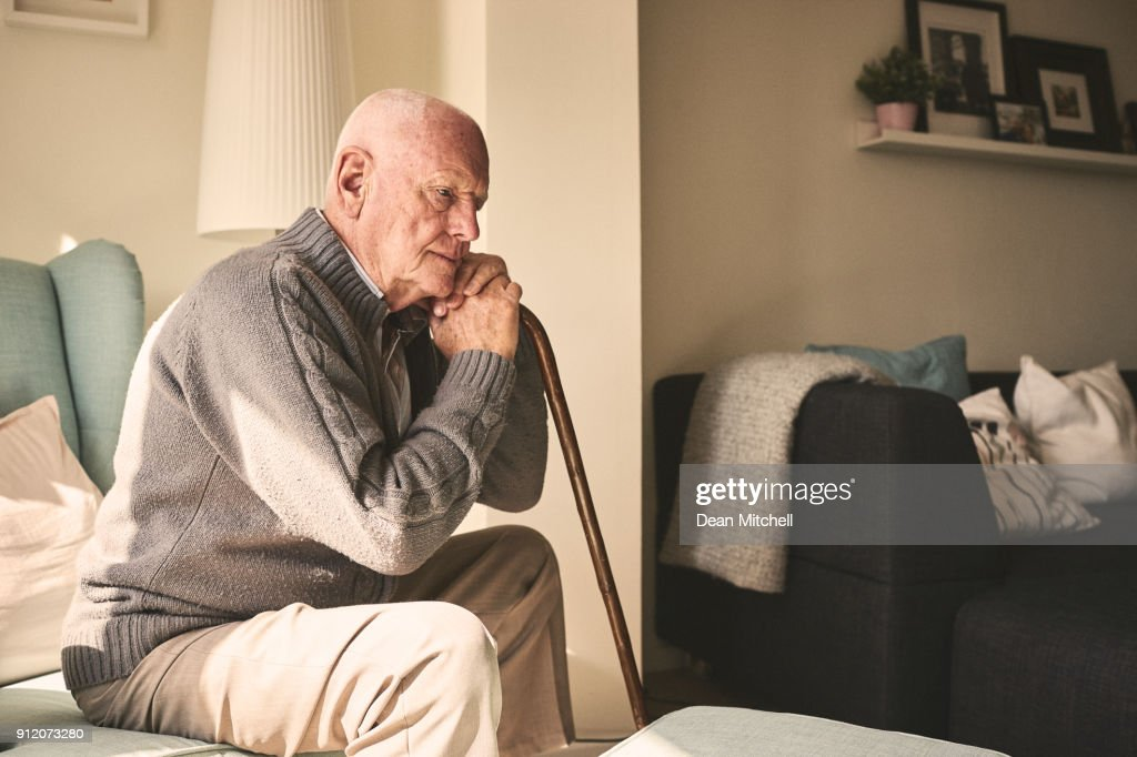 Elderly man sitting alone at home : Stock Photo