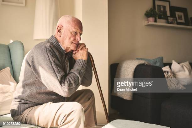 elderly man sitting alone at home - senior adult stock pictures, royalty-free photos & images