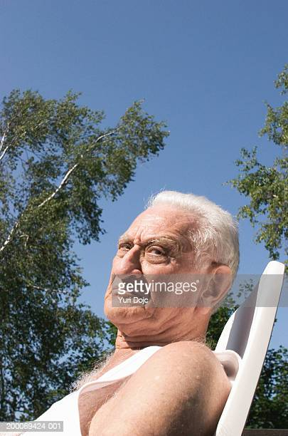 Elderly man sitting in chair, side view, close up