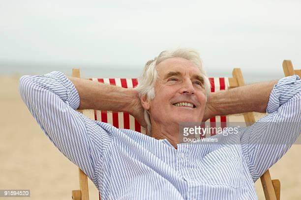Elderly man sitting in deck chair at beach.