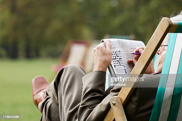 Elderly man sitting in deckchair outside doing crossword