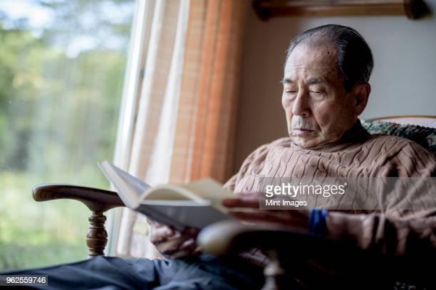 elderly man sitting in rocking chair by a window, reading book. - 社会問題 ストックフォトと画像