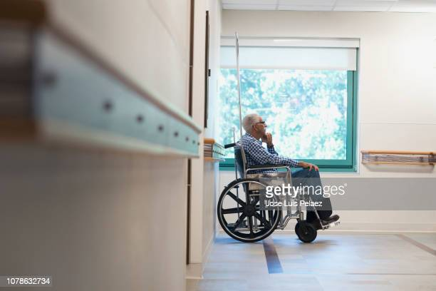 elderly man sitting in wheelchair in hospital - african american man helping elderly stock pictures, royalty-free photos & images