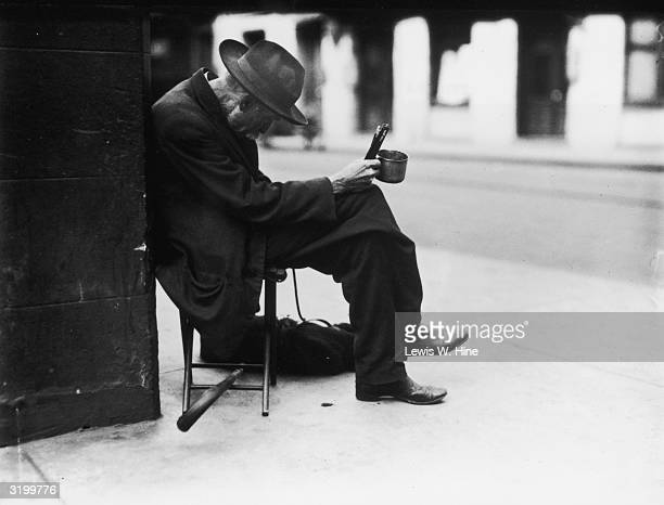Elderly man sitting on a stool on a street corner holding out a tin cup and bowing his head