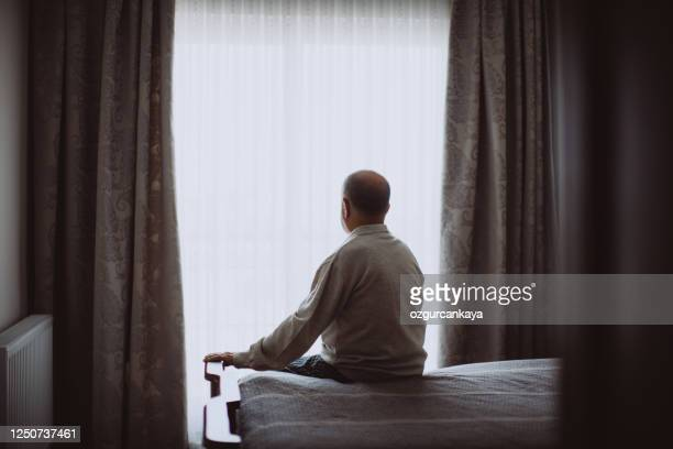elderly man sitting on bed looking serious - solitude stock pictures, royalty-free photos & images