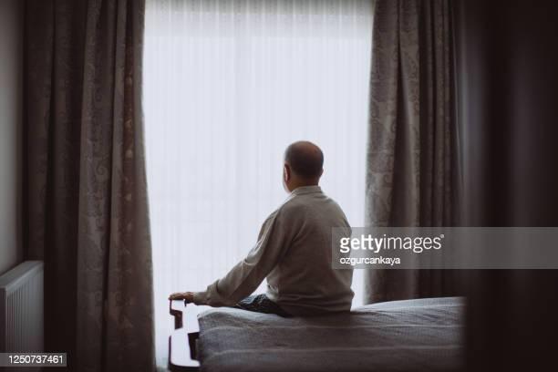 bejaarde zitting op bed dat ernstig kijkt - eenzaamheid stockfoto's en -beelden