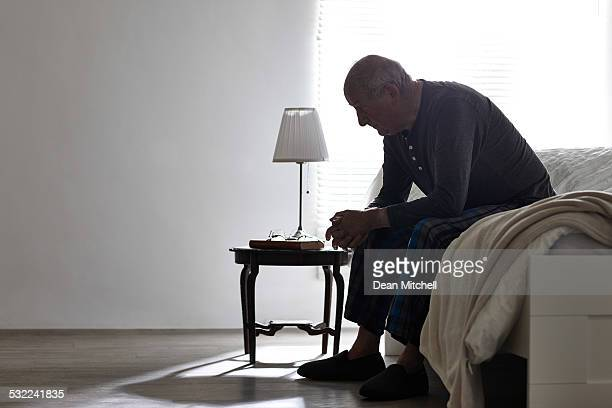 elderly man sitting on bed looking serious - sadness stock pictures, royalty-free photos & images