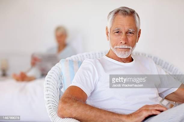 Älterer Mann sitzt auf einem Stuhl