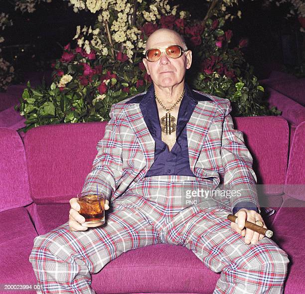 elderly man sitting on couch with cocktail and cigar, portrait - fashion oddities stock pictures, royalty-free photos & images