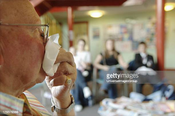 Elderly man sneezing in crowded waiting room of doctors surgery