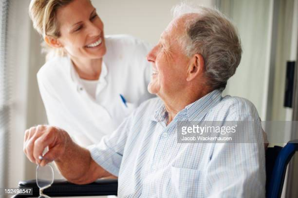 elderly man speaking to a nurse - bejaard stockfoto's en -beelden