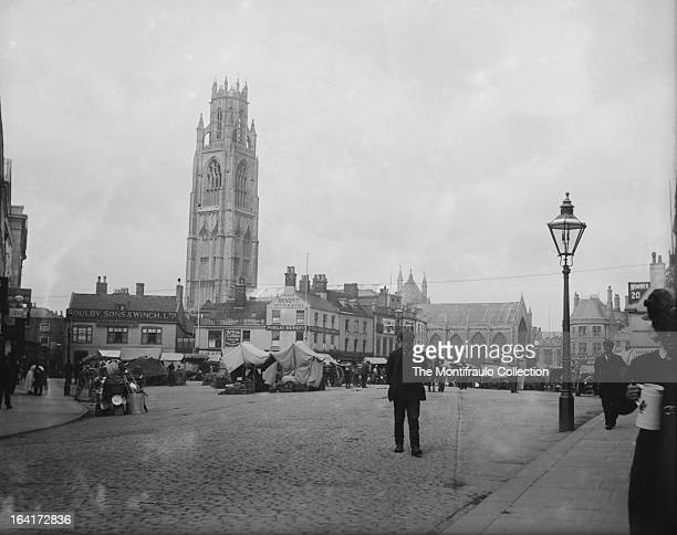Elderly man standing in busy market square of Boston town inLincolnshire with St Botolph's church famous for its tall tower knownas the Boston Stump...