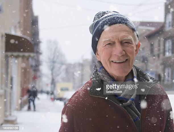 Elderly man standing on sidewalk during snow storm