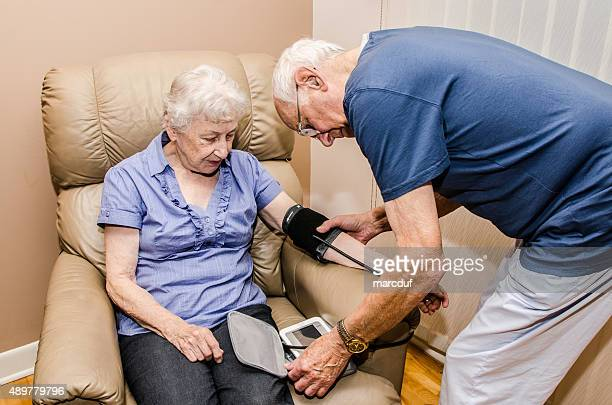 elderly man taking blood pressure of his wife - reclining chair stock photos and pictures