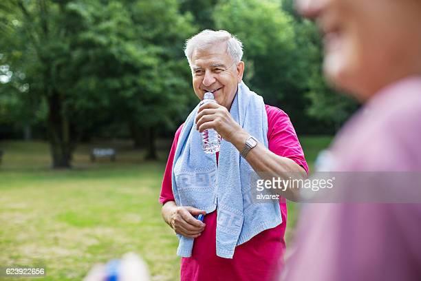 Elderly man taking break from workout in park