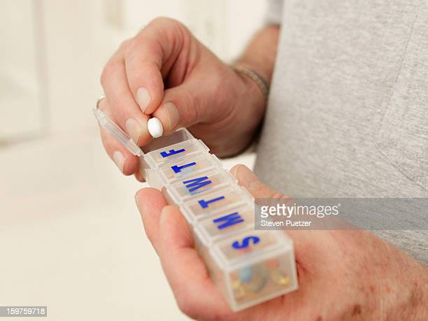 Elderly man taking pill out of container