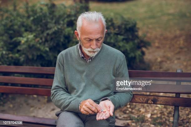 oudere man met voorschriftgeneeskunde in het park - medicijnen innemen stockfoto's en -beelden