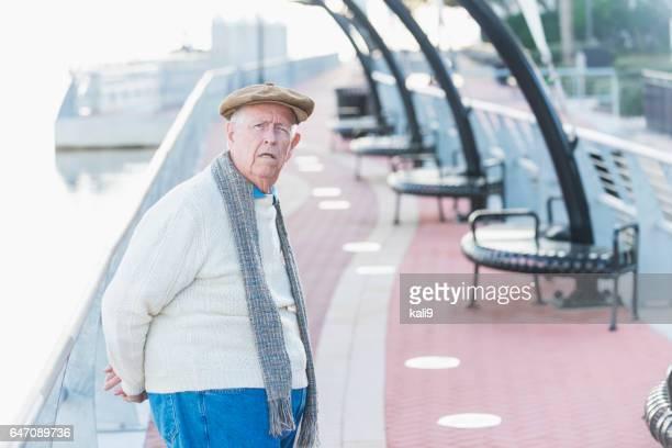 Elderly man taking walk on pedestrian walkway