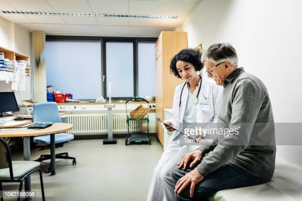 elderly man talking to doctor about test results - patiënt stockfoto's en -beelden