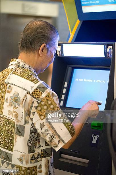 Elderly man uses an ATM