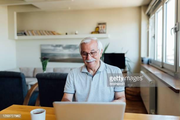 bejaarde die laptop thuis gebruikt - alleen seniore mannen stockfoto's en -beelden