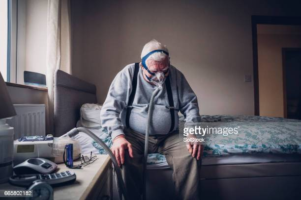 elderly man using a medical breathing apparatus - medical condition stock pictures, royalty-free photos & images