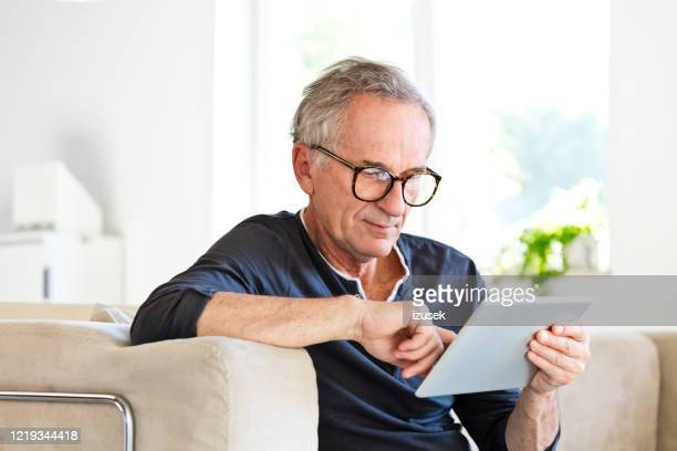 elderly man using digital tablet together at home - digital tablet stock pictures, royalty-free photos & images