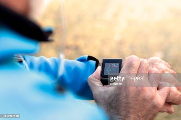 elderly man using smart watch measuring heart rate - healthy lifestyle stock pictures, royalty-free photos & images
