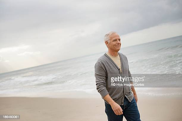 elderly man walking along beach - three quarter length stock pictures, royalty-free photos & images