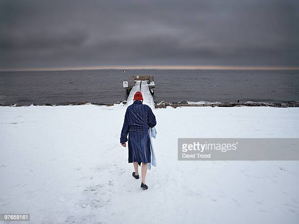 elderly man walking towards to sea in the snow - danemark photos et images de collection