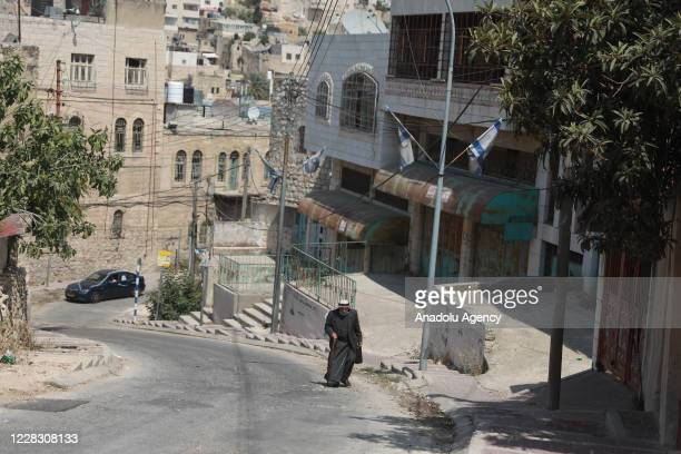 Elderly man walks past a street in Hebron, West Bank on September 01, 2020. Palestinians in the city of Hebron, live under difficult conditions in...